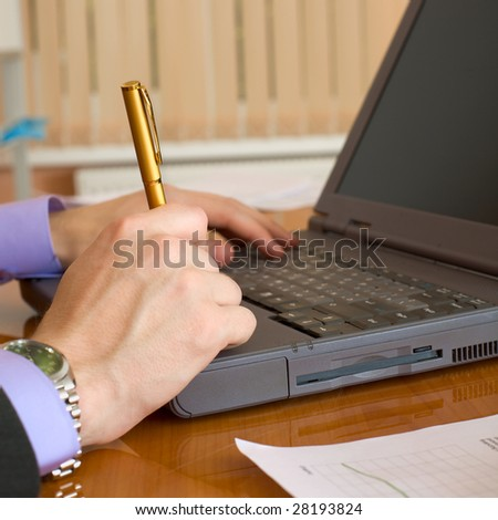 Laptop and man's hands with a pen - stock photo