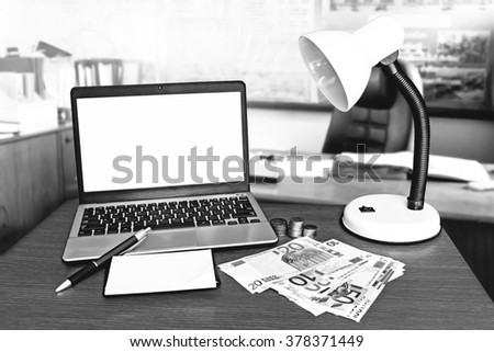 laptop and money with blur table in office background
