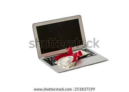 Laptop and money with red ribbon - stock photo