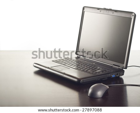 laptop and mouse on shiny table - stock photo