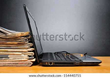 Laptop and newspapers on a table with black background - stock photo