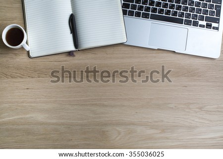 Laptop and Notepad with pen on a wooden surface. - stock photo