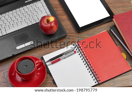 Laptop and office supplies on wooden table - stock photo