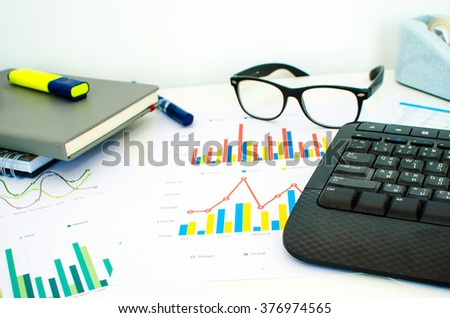 laptop and pen with  business charts, graphs, statistic and documents