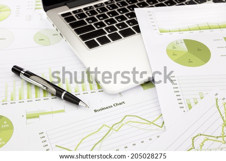 laptop and pen with green business charts, graphs, information and reports background for financial and business concepts - stock photo