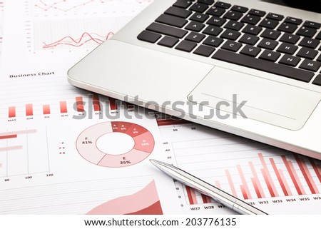 laptop and pen with red business charts, graphs, information and reports background for financial and business concepts - stock photo