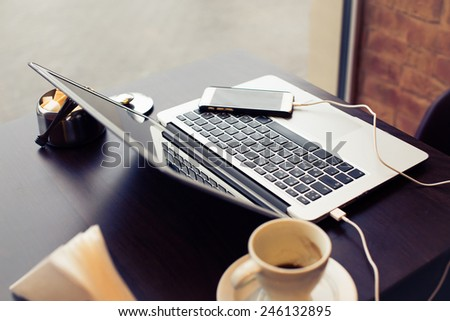 Laptop and phone on a table with sugar bowl and coffee cup - stock photo