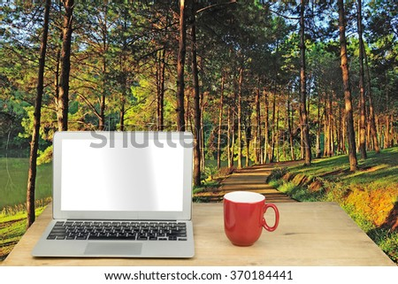 laptop and red mug on wood table with forest pine - stock photo