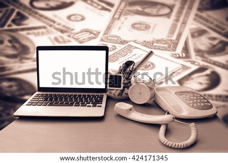 laptop and telephone with blur dollar banknotes background - stock photo