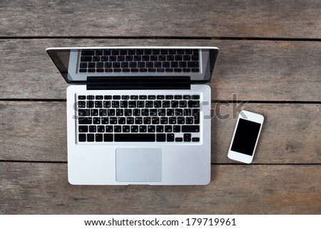 laptop and white smartphone on old wooden desk - stock photo
