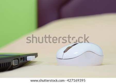 Laptop and wireless mouse on bed