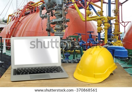 laptop and yellow safety helmet on wood table with oil tank - stock photo