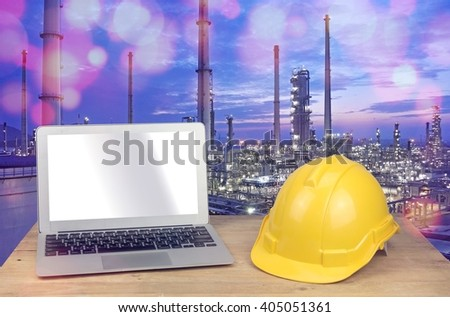 laptop and yellow safety helmet on wood table with refinery - stock photo