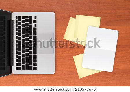Laptop and yellow sticky posts and white, blank note book on modern, wooden office table. - stock photo