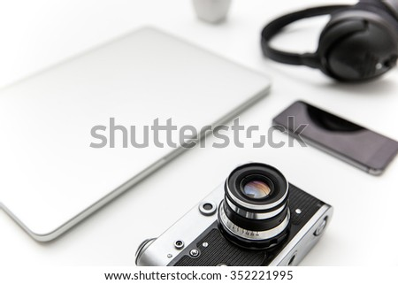 Laptop, blank screen smartphone, old camera, and headphones over white background