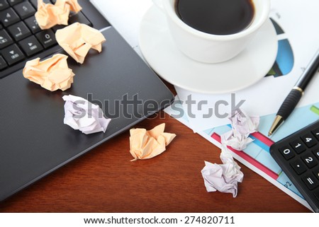 Laptop, calculator, cup of coffee and crumpled paper on the table - stock photo