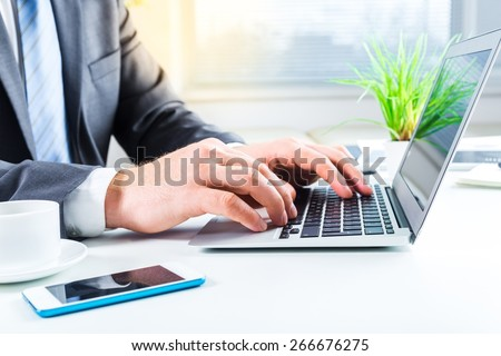 Laptop. Close up of business man hands typing on laptop computer - stock photo