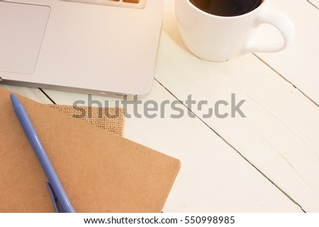 laptop, coffee cups, pens, books, put on white wood