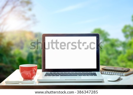 Laptop computer and coffee on workspace and mountain at morning fresh background, - stock photo