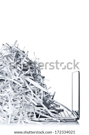 Laptop computer and shredded paper  - stock photo