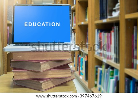 laptop computer education font with on old book in library room - stock photo