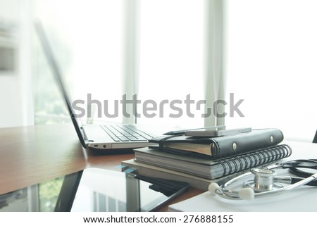 laptop computer in medical workspace office and smart phone as doctor workplace concept - stock photo