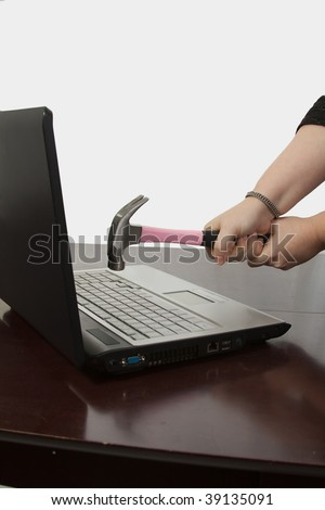 Laptop computer on a brown desk and a pair of hands holding a pink hammer over keyboard