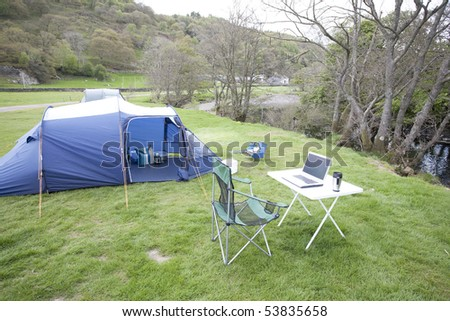 laptop computer on a table next to a tent for outdoor computing - stock photo