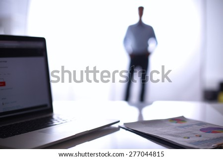Laptop computer on desk , one businesman standing in the background - stock photo