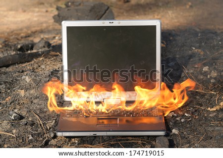 Laptop Computer on fire - stock photo