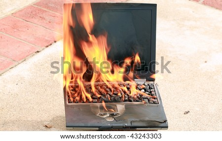 laptop computer on fire, represents computer damage, loss of data, emergency and more - stock photo