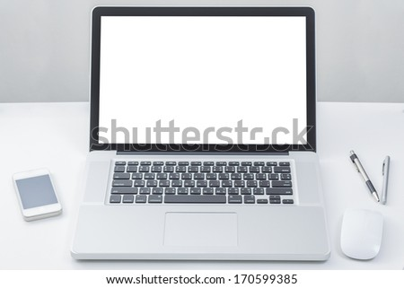 Laptop computer on table with blank screen - stock photo