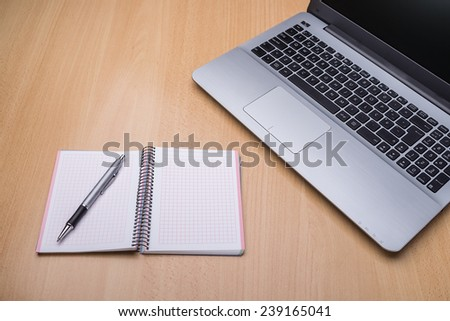 Laptop computer on the desk in the office. Notebook for recording. - stock photo
