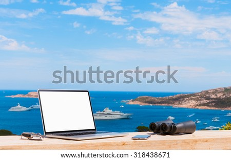Laptop computer on wood table with sea background