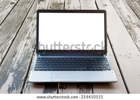 Laptop computer on wooden floor with blank screen