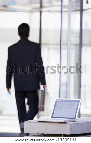 Laptop computer outside office with businessman in background - stock photo