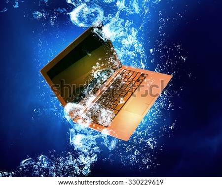 Laptop computer sink in clear blue water