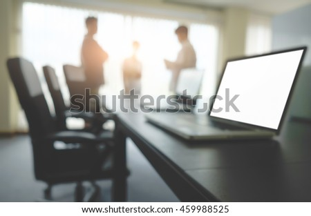 Laptop computer with blank white screen ready for content on wooden desk in meeting with  business people discussing the charts and graphs background, selective focus. Business concept.   - stock photo