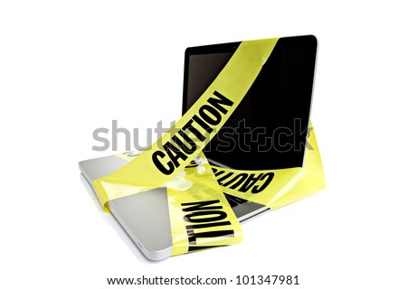 Laptop computer with caution tape wrapped around it