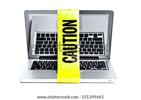 Laptop computer with caution tape wrapped around it - stock photo