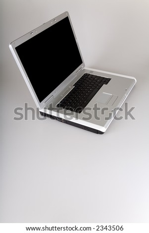 Laptop computer with cut-out black screen. View from top with space for text at the bottom. - stock photo