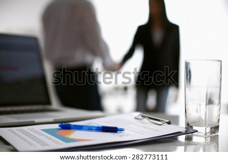 Laptop  computer with folder on the desk ,two  businesspeople standing in the background. - stock photo