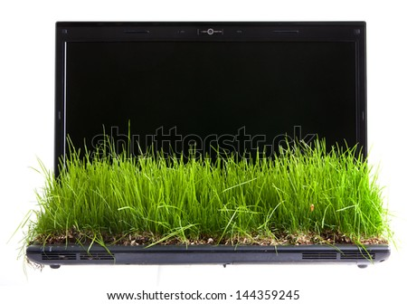Laptop computer with  green grass growing on keyboard isolated on white.  - stock photo
