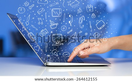 Laptop computer with hand drawn icons and symbols comming out - stock photo