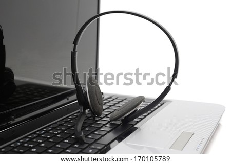 Laptop computer with headset on keyboard - stock photo