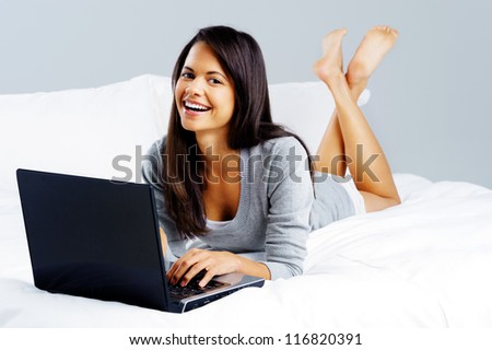 Laptop computer woman lying on bed, happy smiling and relaxing at home isolated on grey background - stock photo