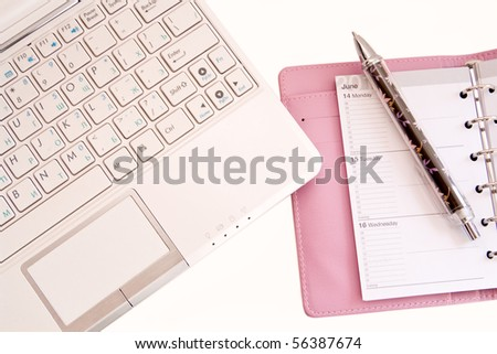 Laptop,  daily log and pen on a white background
