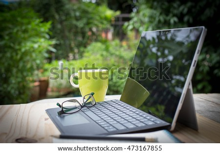 Laptop, glass and other equipments on wooden desk in the garden, selective focus