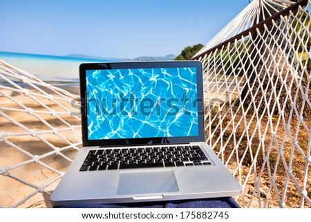 laptop in hammock on the beach - stock photo