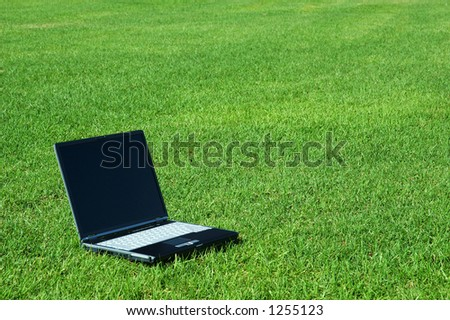 Laptop in the Grass. Laptop Screen is Black. - stock photo